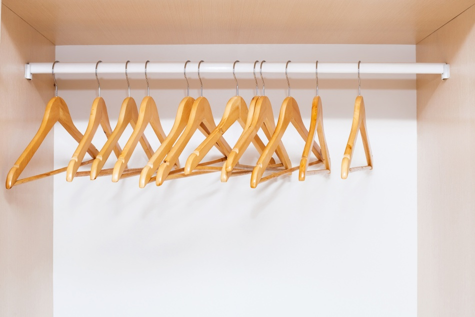 wooden coat hangers on clothes rail